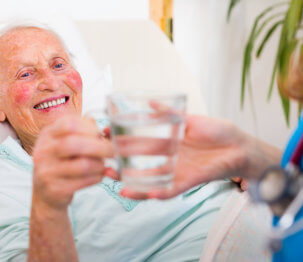 caregiver giving glass of water to elder