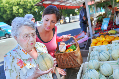 young woman helping elderly woman with grocery shopping
