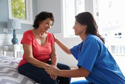 nurse making home visit to senior woman