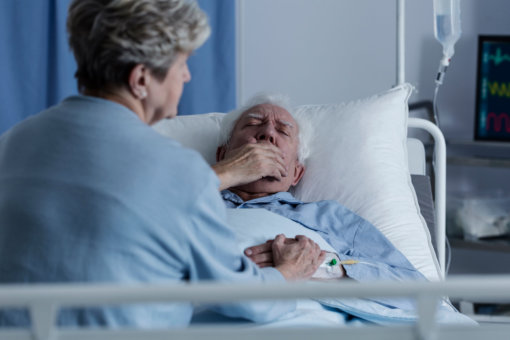 elder man sick in a hospital bed with his wife